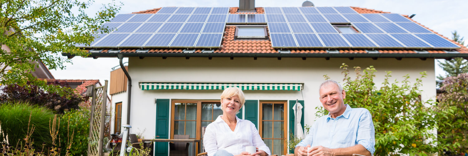Middle aged couple sitting in front of their home with solar panels on the roof